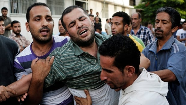 The father of two boys who medics said were killed, along with a girl from the same extended family, by an Israeli air strike grieves outside the morgue in Gaza City on Thursday.