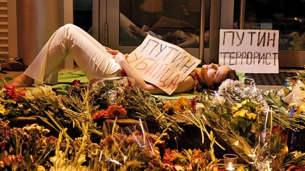 "A woman, holding a sign that reads ""Putin is a murderer"", lies down near flowers left by people at the Dutch embassy in Kyiv to commemorate victims of the Malaysia airliner flight MH17 that was brought down over eastern Ukraine on Thursday, killing all 295 people aboard."