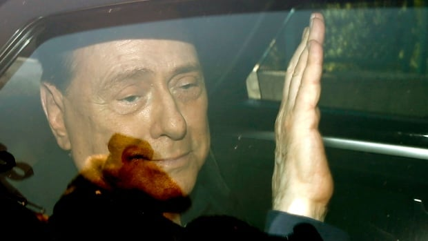 Italy's former premier Silvio Berlusconi waves Friday as he leaves the 'Sacra Famiglia' institute in Cesano Boscone, Italy.  An Italian appeals court has acquitted Berlusconi in a sex-for-hire case.