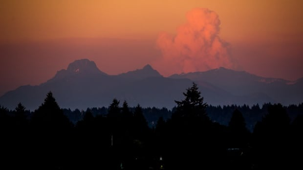 A large cloud rises over wildfires in Central Washington as seen from Seattle's University District at sunset on Wednesday, July 16, 2014. Worsening wildfire activity has prompted the governor's offices in both Washington and Oregon to declare a state of emergency, a move that enables state officials to call up the National Guard. In Washington, that declaration covers 30 eastern Washington counties.