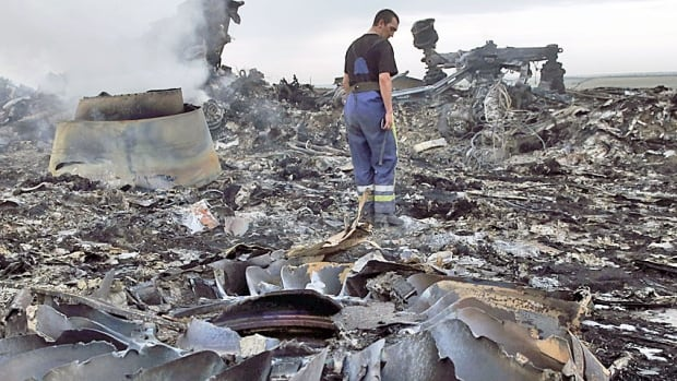 An Emergencies Ministry member walks at the site of a Malaysia Airlines Boeing 777 plane crash near the settlement of Grabovo in the Donetsk region, July 17, 2014. The Malaysian airliner Flight MH17 was brought down over eastern Ukraine on Thursday, killing all 298 people aboard.