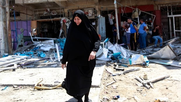 Civilians inspect the site of a bomb attack in the Jihad neighbourhood in Baghdad on Saturday, one of a series of bombings, including three over a span of less than 10 minutes, that killed and wounded dozens across the Iraqi capital.