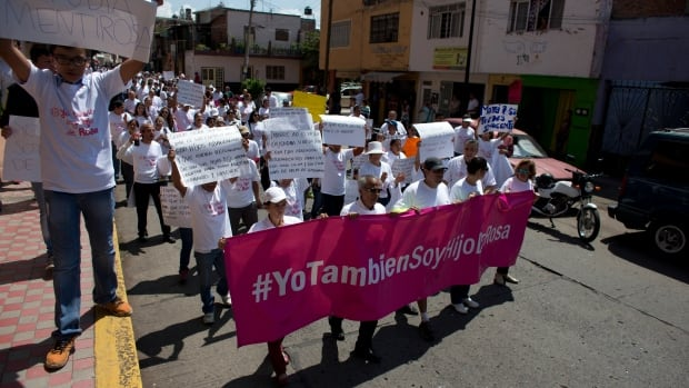 Marchers carry a banner with a message that reads in Spanish, 'I too am a child of Rosa,' as they march in support of Rosa del Carmen Verduzco, founder of the The Great Family group home in Zamora, Mexico, on Thursday. A raid and arrests of Verdozco and home workers on allegations of abuse, mistreatment and filthy conditions have divided the country.