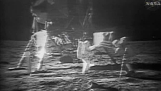 American astronauts Neil Armstrong and Buzz Aldrin walk on the moon, the first humans to set foot on it.