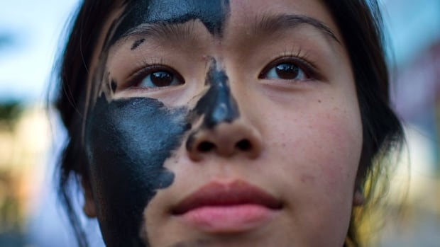 An activist wears face paint to simulate oil while attending a rally in Vancouver opposition to the Enbridge Northern Gateway pipeline. The Harper Conservatives have made the pipeline a key plank in their energy strategy, but a federally commissioned focus-group report says the public has 'little enthusiasm' for the project.