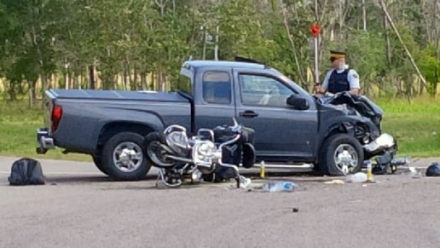 An RCMP officer investigates at the scene of a crash at Highway 44 and Highway 11 Sunday afternoon. Two people were killed.