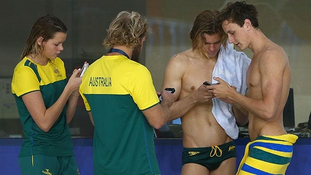 Members of the Australian team check their phones during a training session at Tollcross International Swimming Centre.