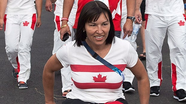 Chef de mission Chantal Petitclerc  leads the way as the Canadian team arrives at its welcome ceremony at the Commonwealth Games in Glasgow, Scotland on Monday.