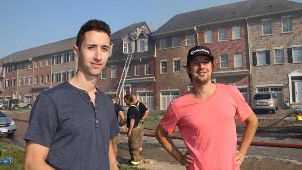 Jonathan and Andrew More stand in front of their units at 342 and 344 Louisa St. Both brothers were woken up early Tuesday morning by firefighters knocking on their door to get them to leave their units. The roof of Jonathan's unit was destroyed.