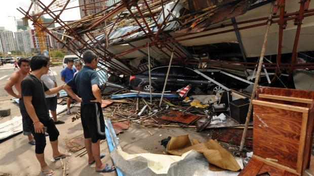 In this photo released by China's Xinhua News Agency, a vehicle sits under a collapsed building after landfall of typhoon Rammasun in Haikou, capital of south China's Hainan Province. China's Civil Affairs Ministry said Typhoon Rammasun has caused floods, hail showers and mudslides since it made landfall Friday.