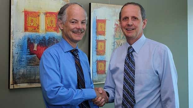 Dr. Malcolm Maclure poses for a photo with deputy health minister Stephen Brown, which was released by the government on Friday.