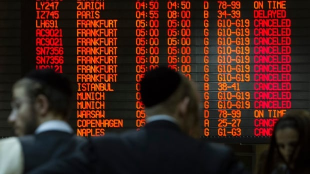 A departure time flight board displays various cancellations as passengers stand nearby at Ben Gurion International airport in Tel Aviv  July 22, 2014. The Federal Aviation Administration (FAA) banned U.S. carriers from flying to or from Ben Gurion International Airport, after a rocket fired from Gaza struck near the airport's fringes, injuring two people. European airlines including Germany's Lufthansa, Air France and Dutch airline KLM said they were halting flights there too. Israel's flagship carrier El Al continued flights as usual.