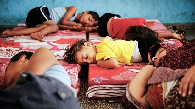 Palestinians sleep at a UN school to escape heavy Israeli shelling in the Shejaia neighbourhood in Gaza City on Monday.