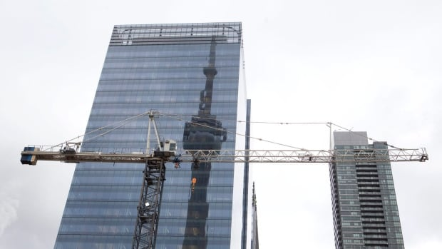 The CN tower is reflected in a high rise condo under construction. The Toronto condo market is booming again after a hiatus in 2013.