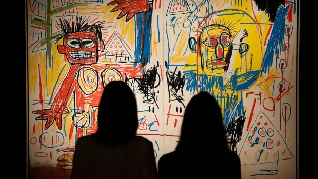 Visitors are seen gazing at a Jean-Michel Basquiat painting at London's Christie auction house in June of 2013. A new exhibit of the late U.S. artist's work will be coming to the Art Gallery of Ontario in February 2015.