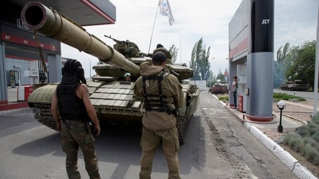 Rebels in the  Donetsk People's Republic fill their tank with fuel at a gas station in Snizhne, 100 kilometres east of Donetsk, eastern Ukraine.