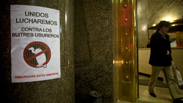 "A sign in Spanish posted on a wall at the Argentine Economy Ministry reads: ""Together we will fight against the loan shark vultures,"" referring to an unresolved dispute over $1.5 billion in unpaid debts. Argentina will default for the second time in 13 years if it cannot reach a deal with the U.S. hedge funds before July 30."