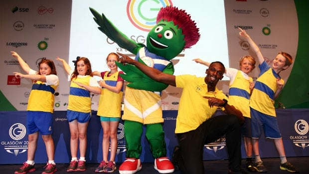 Sprinter Usain Bolt of Jamaica, kneeling, poses with Clyde the mascot and children after arriving at a press conference at the 2014 Commonwealth Games.