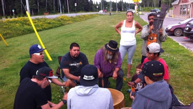 Beau Dick (centre) and Guujaaw, who is holding the copper shield, meet with community members in Wawa, Ont., on their way from Vancouver to Ottawa.