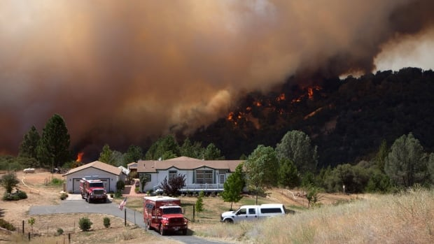"Firefighters protect an evacuated home while the fast-moving wildfire called ""Sand Fire"" burns behind near Plymouth, California."