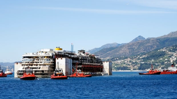 Tug boats tow the Costa Concordia to Genoa's port in northern Italy, where the ship will be broken up for scrap.