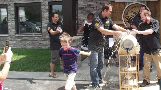 Tapping the keg. The Petit-Sault Brewers make their beer out of an old police station in Edmundston's downtown.