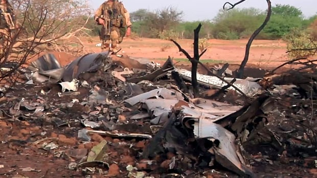 This photo provided by the French army shows soldiers on Friday at the site of the plane crash in Mali, in which five Canadians were among 118 people killed.