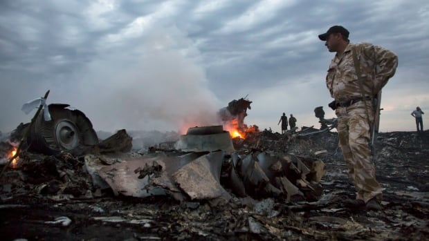 People walk amid the crash site of Malaysia Airlines Flight MH17 earlier this month. A team of Dutch and Australians who will investigate the site have been turned back for a third straight day due to heavy fighting.
