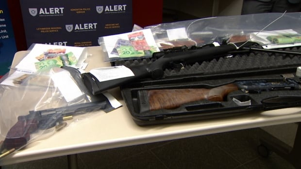 Police put several weapons on display that were seized, along with illegal drugs and cash, in a joint operation among RCMP, ALERT and Calgary police.
