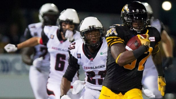 Hamilton Tiger-Cats running back C.J. Gable, right, is pursued by several Ottawa RedBlacks during an 83-yard reception that would lead to the game-winning touchdown late in the fourth quarter in their CFL home opener in Hamilton, Ont., Saturday, July 26, 2014.