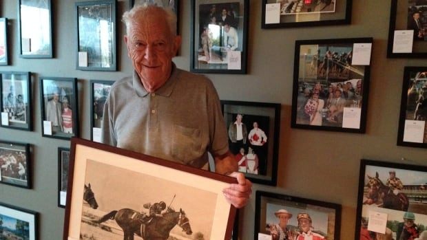 Ralph Bower poses on July 31, 2014, with one of his historic photographs at a new exhibit at Hastings Racecourse.