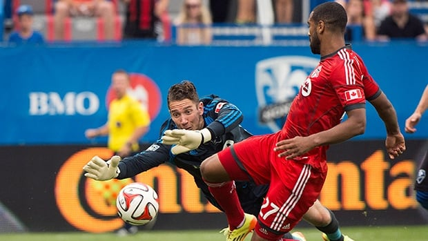 Impact keeper Troy Perkins, left, fails to stop Luke Moore (27) from scoring in a 2-0 loss to Toronto FC at Saputo Stadium.