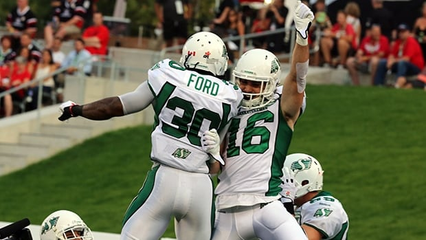 Brett Swain (16) and Will Ford (30) of the Roughriders celebrate a touchdown in a 38-14 rout of the Redblacks on Saturday.
