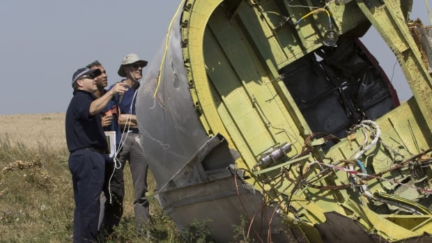 Australian and Dutch experts examine a piece of the downed Malaysia Airlines jet, near the village of Hrabove in eastern Ukraine.