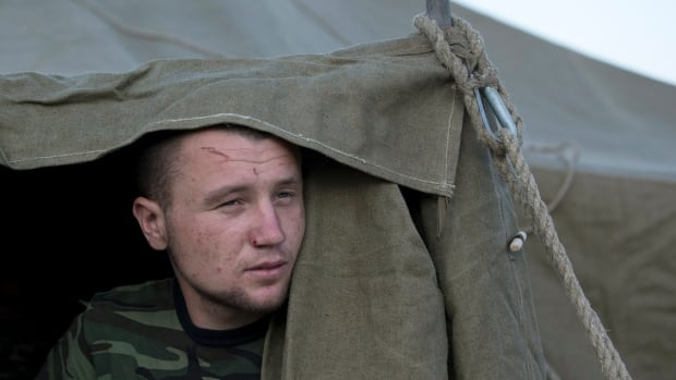 A Ukrainian soldier, who fled the conflict territory, looks out from a tent at the camp near the Russia-Ukraine border just outside the village of Gukovo, Russia, on Monday. Pro-Russian separatists opened fire on unarmed Ukrainian soldiers as they crossed back into Ukraine from Russia, Kyiv defence officials said.