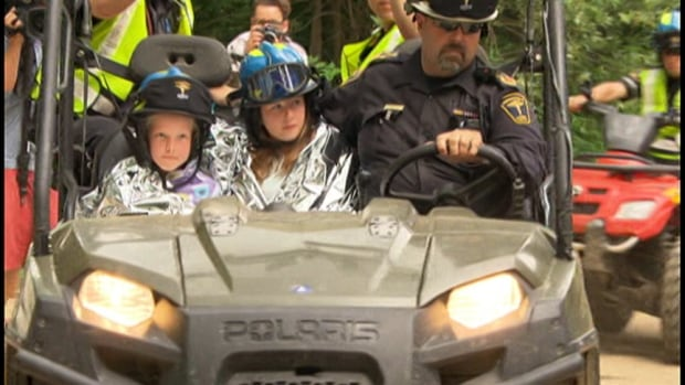 Elya Munro and Ember Greatrix emerge from the bush in Aird Lake, Ont., after spending a night outside after getting lost. Police said the girls were found when they heard search crews looking for them and yelled back.