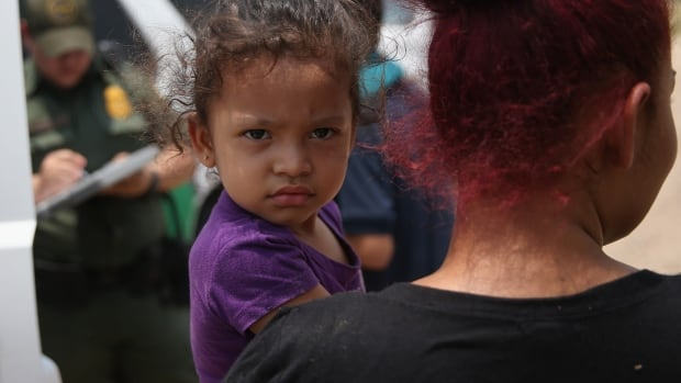 U.S. Vice President pleaded with American lawyers for pro bono help with the country's child migrant crisis. Here, a mother and her 3-year-old from El Salvador await transport to a processing centre for undocumented immigrants after they the Mexico-Texas border.
