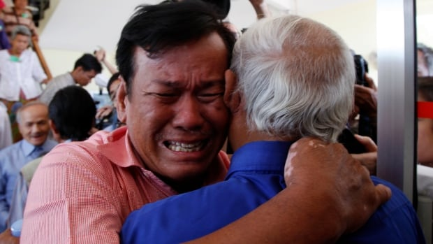 Two Cambodians whose families fell victim to Khmer Rouge atrocities in the 1970s embrace after a tribunal sentenced the group's last two surviving leaders to life in prison for war crimes.
