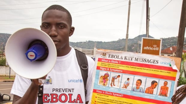 "A man and woman give information about Ebola in Sierra Leone. In the country's east, the head of police said security forces deployed last night ""to establish a complete blockade,"" setting up 16 checkpoints on major roads."