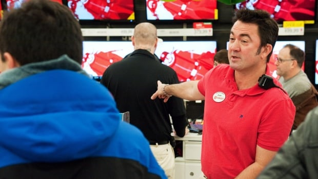 Target team member Shawn Ladner helps shoppers in the electronics department.  The company is mounting a defence of gay marriage saying states that won't recognize it cause problems with employee benefits.