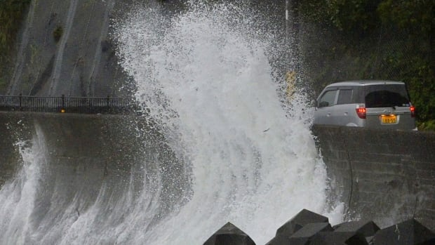 A big sea wave hit against a concrete wall to a road in Kushimoto, western Japan, Saturday, Aug. 9, 2014.