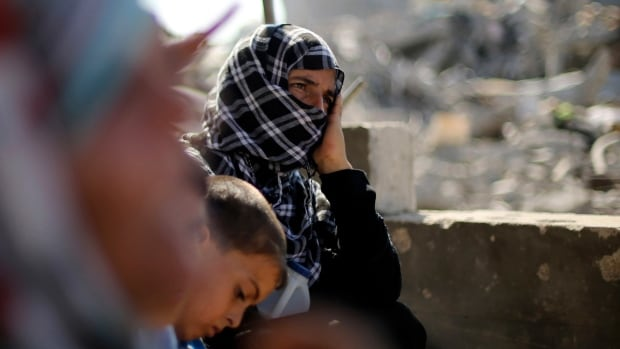 Palestinians sit on the remains of their house, which witnesses said was destroyed in the Israeli offensive. So far, peace talks in Egypt have been fruitless.