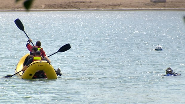 Emergency responders slowly paddle through Sikome Lake on Tuesday looking for a missing 29-year-old man, who was later found dead.