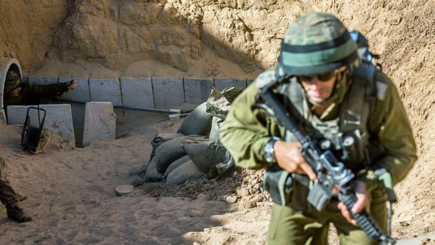 Israeli officers emerge from the entrance of a tunnel said to be used by Palestinian militants for cross-border attacks. The warren of tunnels crossing the borders to Gaza have been a central element in the current conflict.