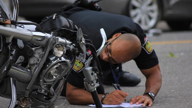 A police officer inspects the scene of a motorbike crash near Watline Avenue and Kennedy Road in Mississauga, Ont.