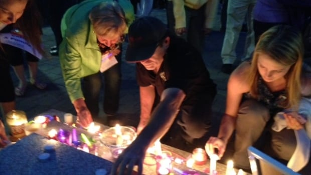 People lighting candles at the Catie Miller vigil.