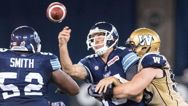 Argonauts quarterback Rickie Ray, middle, makes a pass despite being tackled by the Blue Bombers' Greg Peach during first-half action in Toronto on Tuesday night. Ray got the last laugh, completing 26 of 33 passes for 297 yards and four touchdowns in the Argos' 38-21 win.