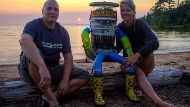 HitchBOT poses with Belgian tourists Seb Leeson and Kim Van Aerde near the halfway mark of its cross-Canada journey.