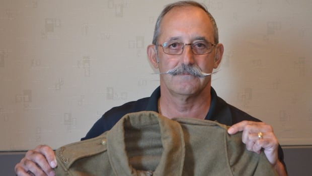 Captain George Romick displays an authentic uniform worn by Canadian soldiers during the First World War, an example of the kind of memorabilia the Centennial Project aims to record.