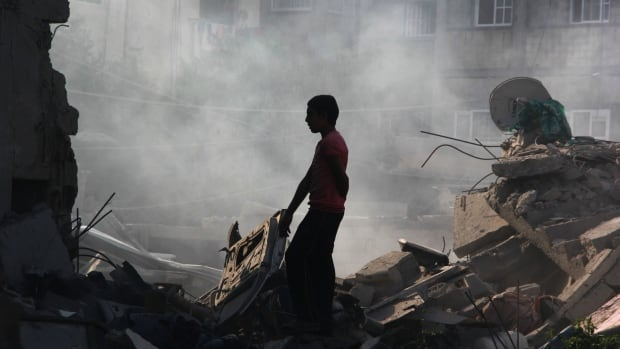 In this Saturday, Aug. 2, 2014 file photo, a Palestinian looks for his belongings after a house was destroyed in an Israeli strike in Rafah, southern Gaza Strip. Israel and Hamas agreed to extend a temporary truce on Wednesday.